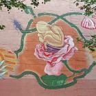 Ein Baby sitzt auf einem Topf in einer Rosenblüte.
